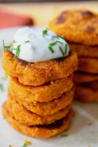 A stack of pumpkin fritters with a blob of white dressing on top.