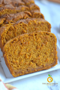A white plate containing slices of pumpkin bread.