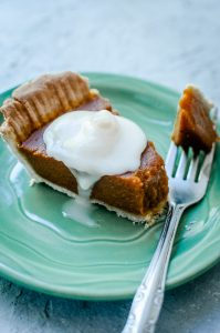 A slice of vegan pumpkin pie, drizzled with cream, on a green plate, with a silver fork.
