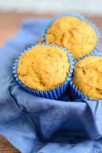 Three pumpkin muffins on a blue cloth.