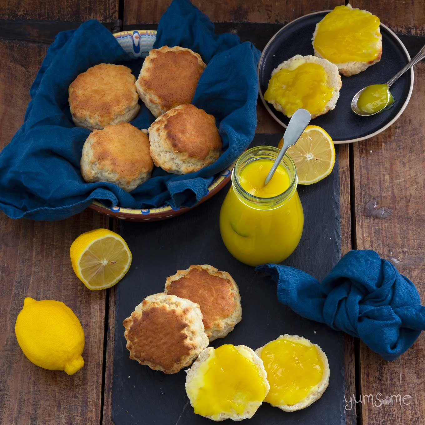 A lot of scones and a jar of lemon curd on a wooden table, along with some blue napkins.