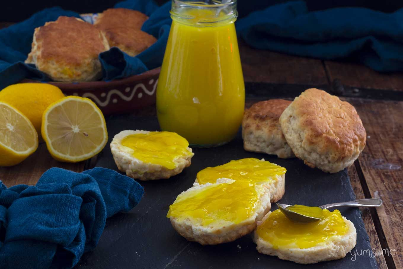 A blue napkin and some scones and lemon curd on a wooden table.