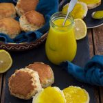 A bowl of whole scones, with some cut open and spread with lemon curd. A jar of lemon curd and some cut lemons are in the background.