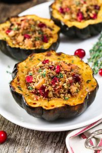 A white plate with three slices of vegan stuffed acorn squash.