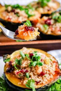 A forkful of quinoa held above a stuffed pumpkin.