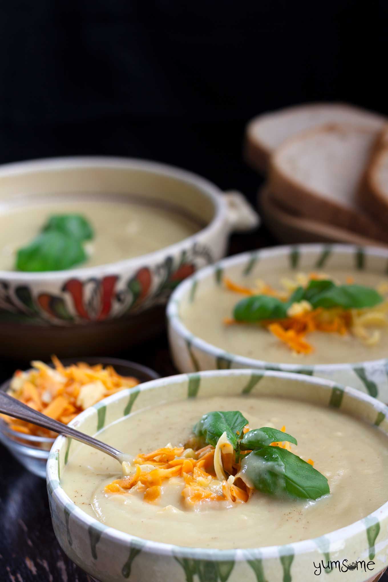 Several bowls of vegan cauliflower cheese soup, garnished with herbs and grated cheese, against a dark background.