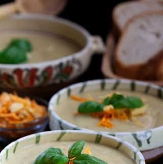 Several bowls of vegan cauliflower cheese soup, garnished with grated cheese and basil, on a black table.