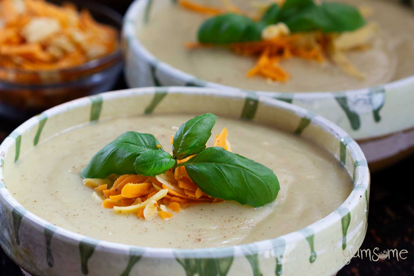 Closeup shot of a bowl of creamy vegan cauliflower soup, garnished with herbs and grated cheese.