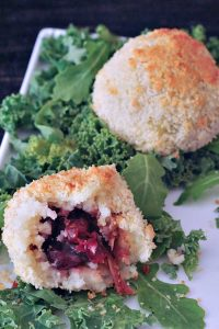 Two crispy stuffed mashed potato balls - one has a bite take out to reveal the deep red filling inside.