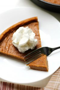 A fork cutting a piece of a wedge of vegan sweet potato pie, with a blob of cream on top.