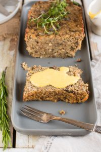 A grey platter with a vegan lentil loaf that has a slice cut from it. The loaf is garnished with herbs, and the slice with a yellow sauce.