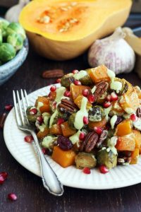 A fork rests on a white plate filled with roasted brussels sprouts and butternut squash.