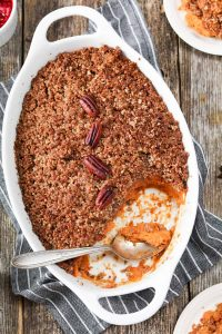 Overhead shot of a white oven dish full of sweet potato casserole with pecan crumble topping.