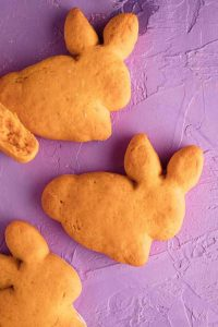 Several biscuits in the shape of bunnies on a purple background.
