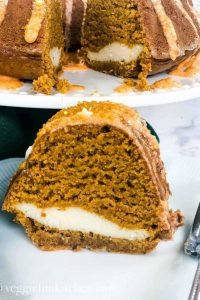 A cut slice of vegan pumpkin cake, with creamy filling.