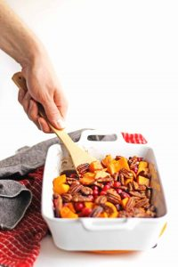 A hand holding a wooden spoon reaches into a white baking dish filled with roasted maple cinnamon butternut squash cubes.