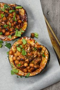 A baking tray lined with greaseproof paper, upon which are two halves of vegan hoisin-glazed stuffed acorn squash.