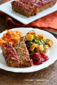 A white plate containing a slice of vegan lentil loaf, some roasted vegetables, and a blob of cranberry sauce. In the background is more lentil loaf on a white platter, and an orange napkin.