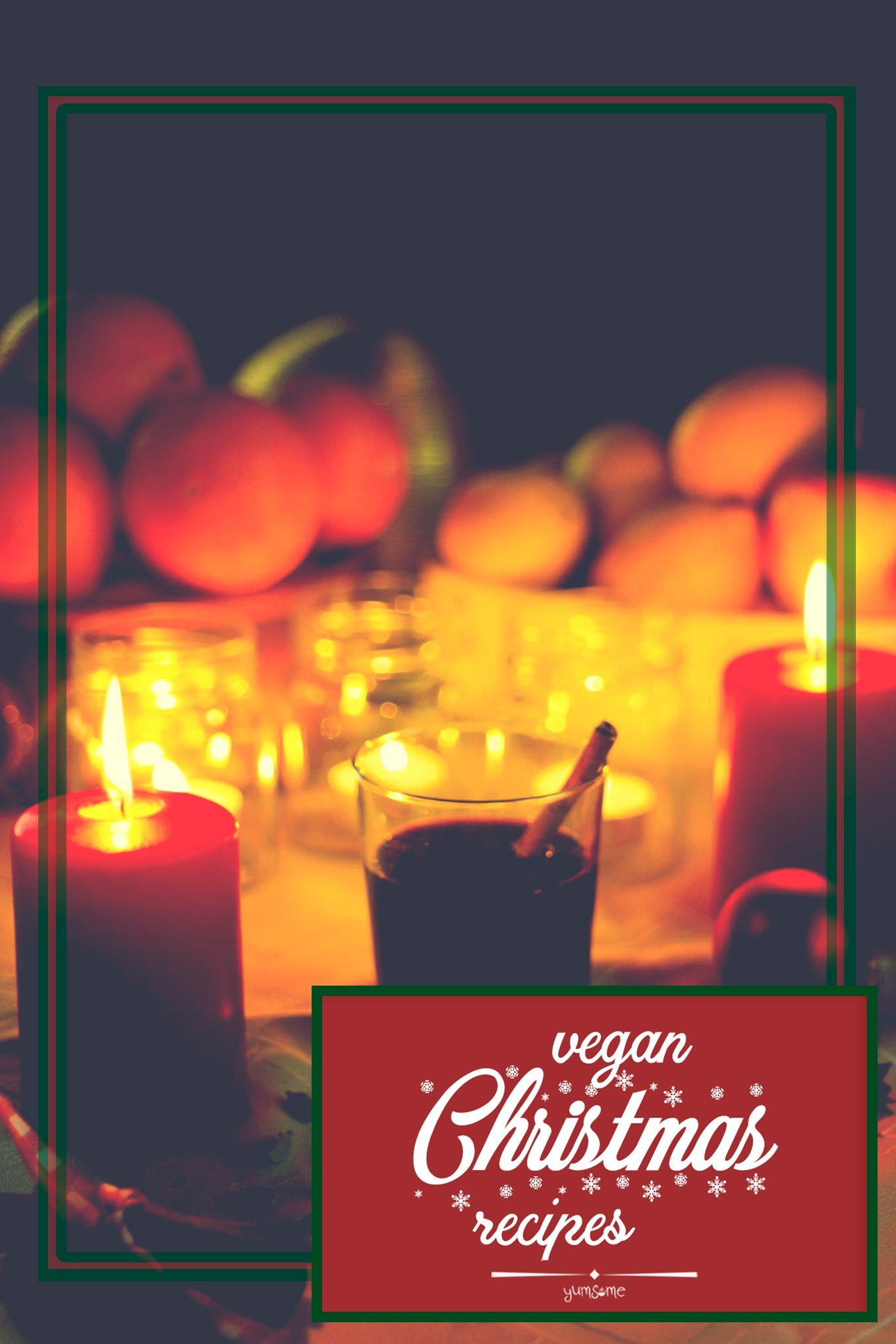 A glass of mulled wine with a cinnamon stick, surrounded by candles and Christmas fruits.