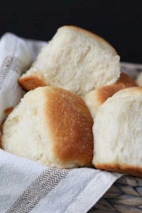 A basket of fluffy vegan dinner rolls.