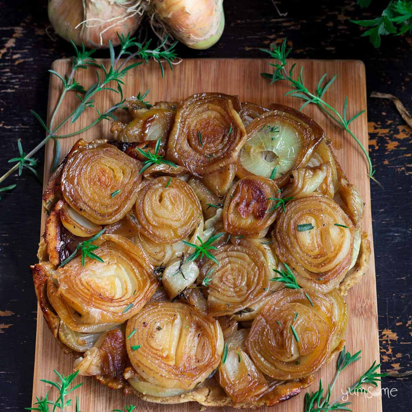 Overhead view of vegan caramelized onion tart on a black table, with some onions and herbs.