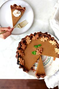Overhead view of a decorated vegan pumpkin pie with a slice removed, and on a plate.