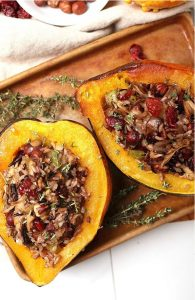 Two halves of Wild Rice Stuffed Acorn Squash on a baking tray.