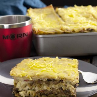 A black plate with a slice of Mariner Valley lasagna, with a tray of lasagna in the background, next to a red MCRN cup.