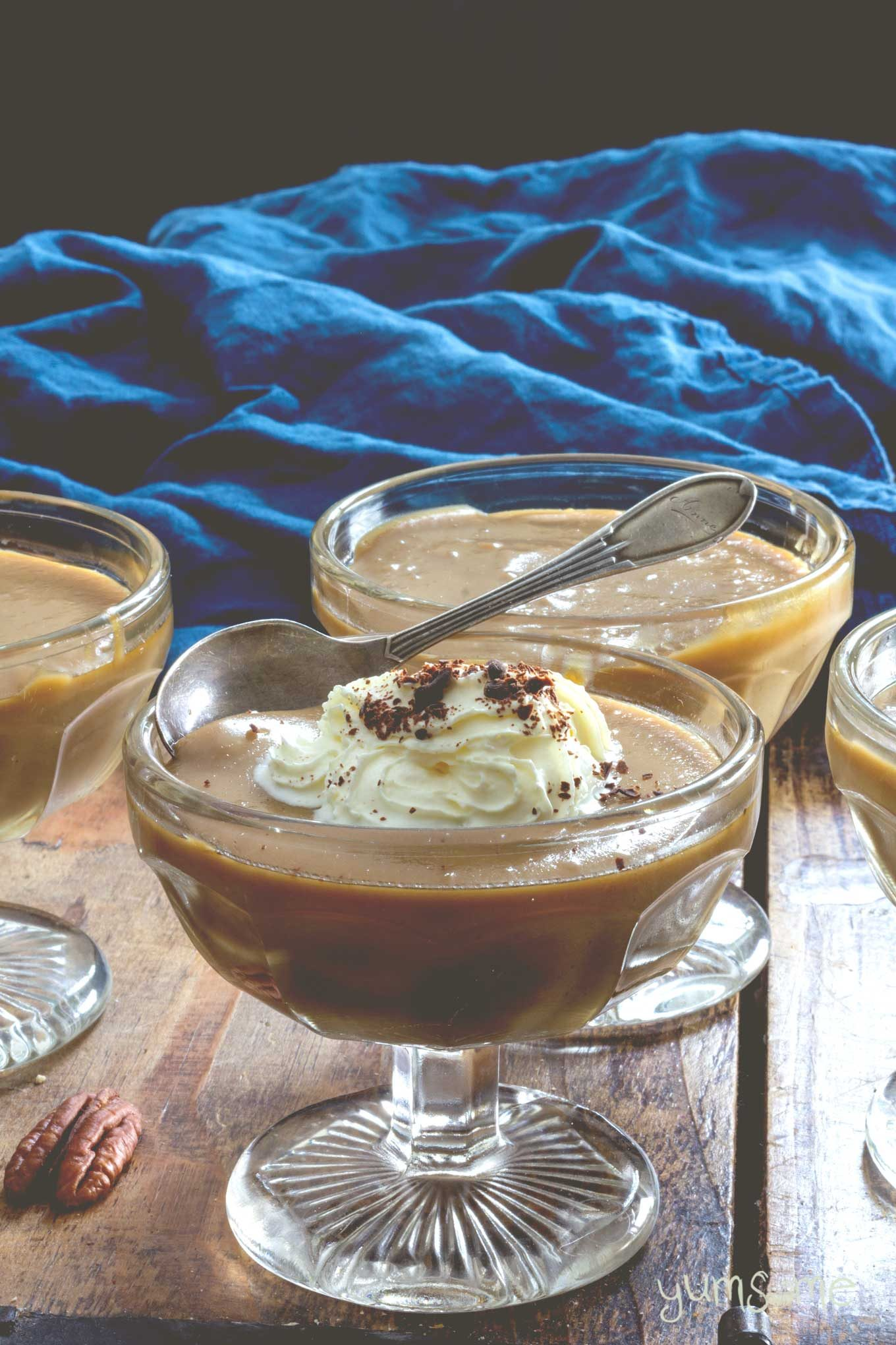 Vegan butterscotch pudding in glass bowls, against a purple and blue background.
