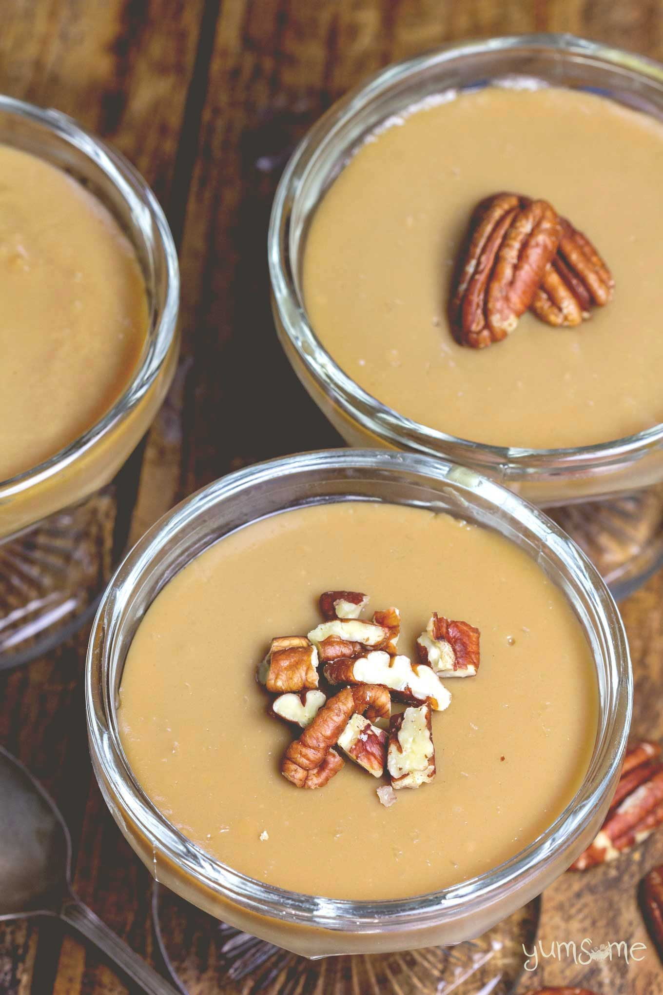 Two bowls of vegan butterscotch pudding, topped with pecans.