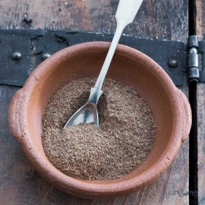 A silver spoon sits in a clay bowl of chai masala.