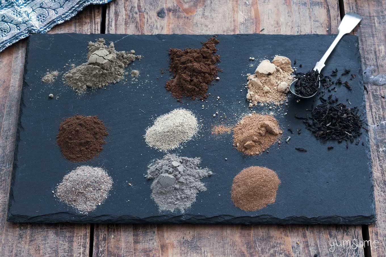Chai masala spices and some black tea on a black slate.