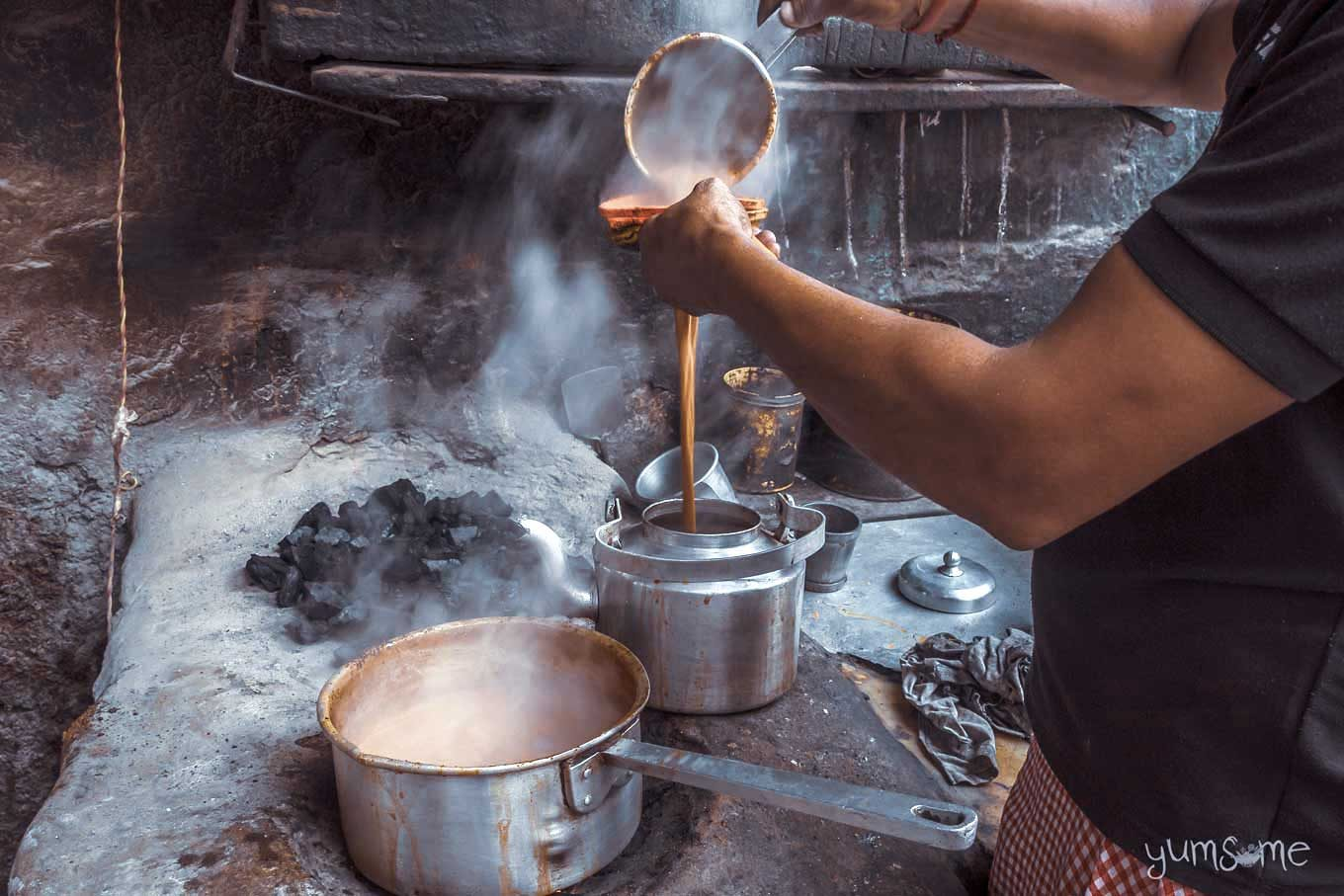 A chai wallah in India straining some masala chai into a large metal teapot.