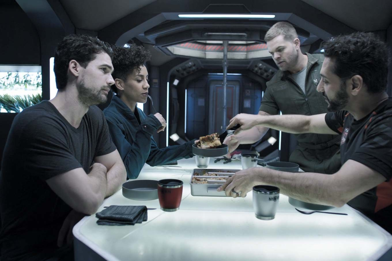 The crew of the Rocinante sitting around the dinner table, as Alex serves Mariner Valley lasagna.