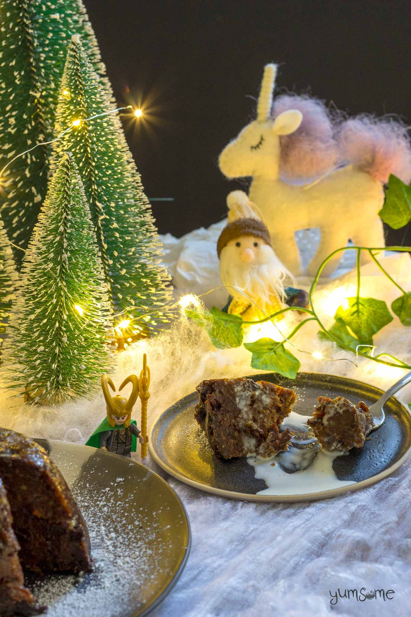 Vegan Christmas pudding on a black plate, with cream drizzled over it.