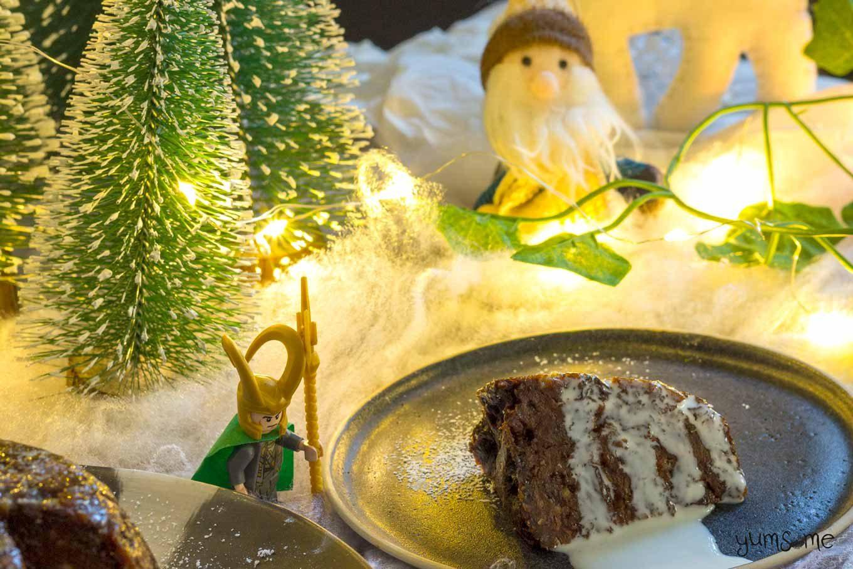 Cream-soaked vegan Christmas pudding on a black plate.