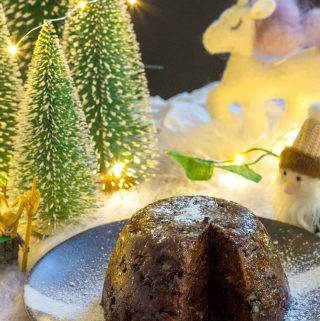 A vegan Christmas pudding, on a black plate, with a slice cut from it.