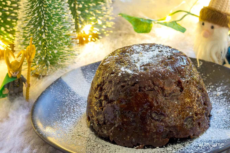 A whole vegan Christmas pudding on a black plate.