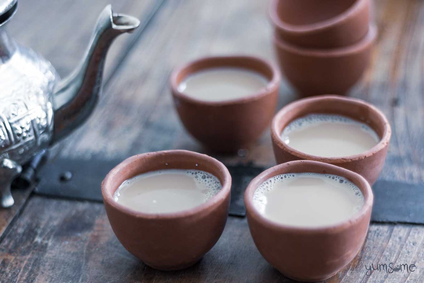 A silver tea pot and four clay cups of masala chai on a wooden table.
