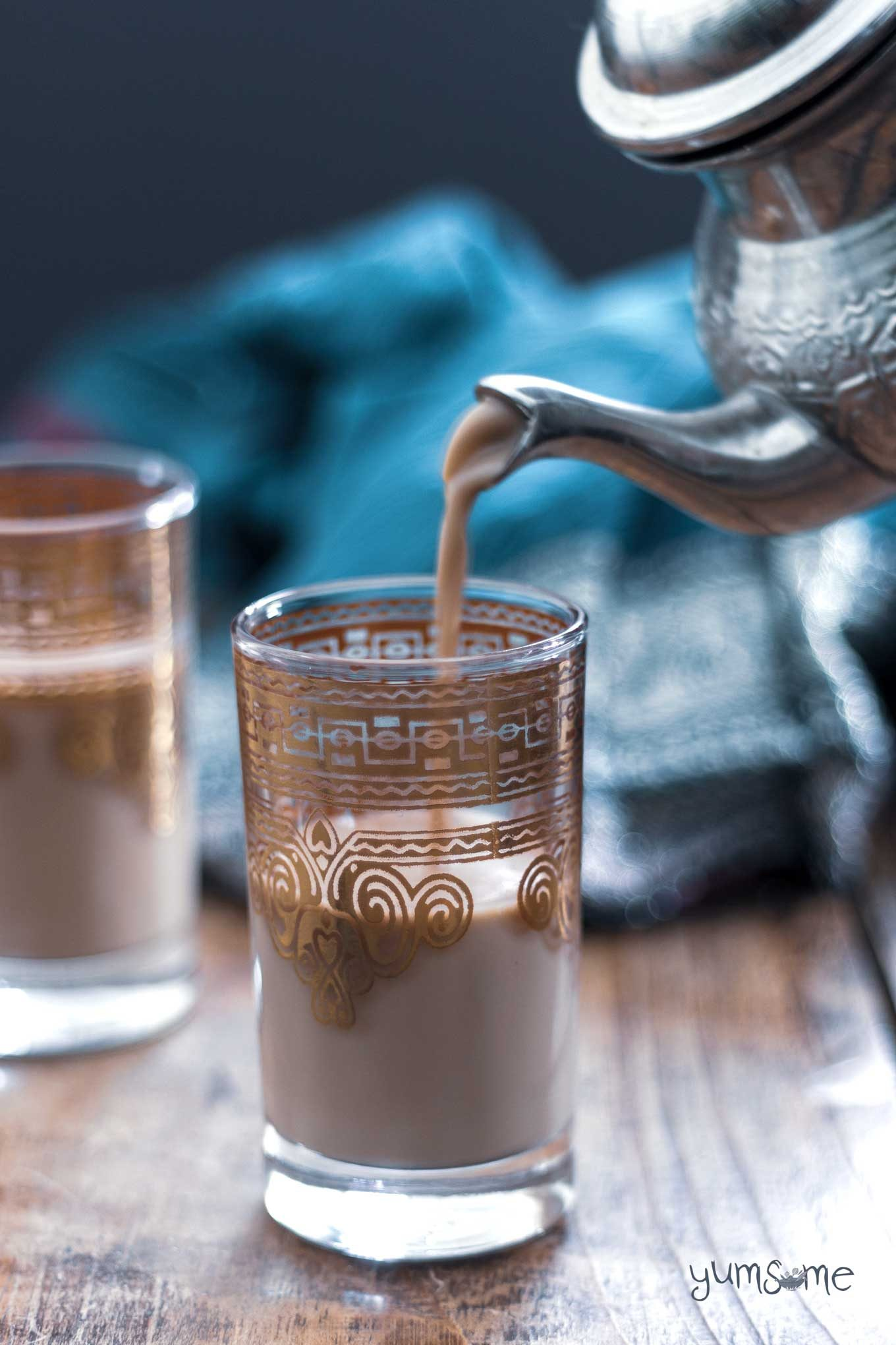 Masala chai being poured into a decorated tea glass from a silver tea pot.