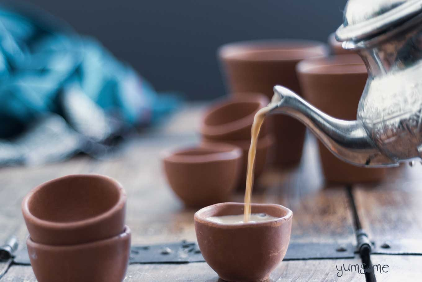 Vegan masala chai being poured into a small kulhar from a silver tea pot.