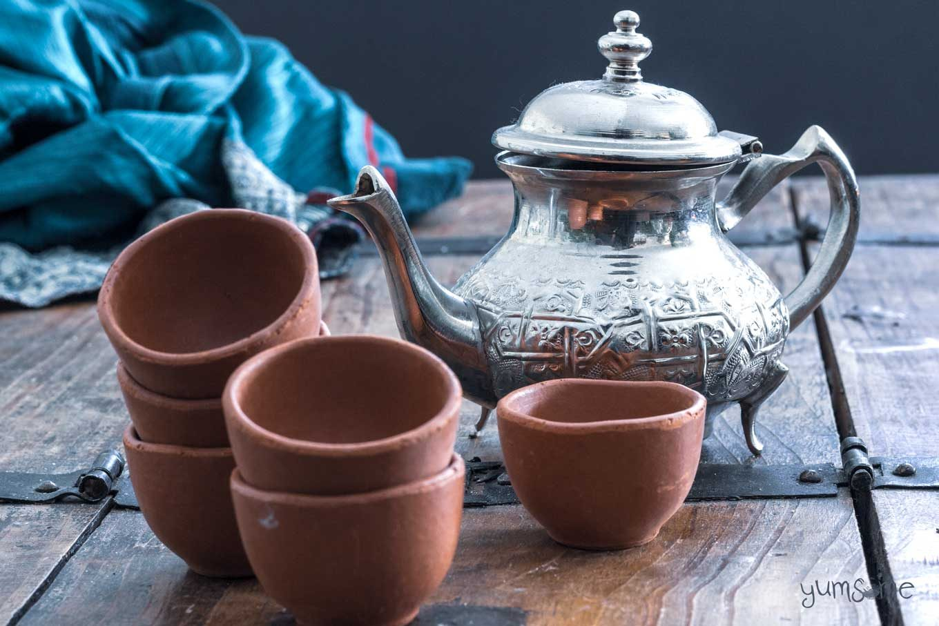 Some small masala chai cups and a silver tea pot on a wooden table, with some bright blue and silver cloth in the background.
