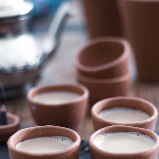 Several small clay cups on a wooden table, containing vegan masala chai.