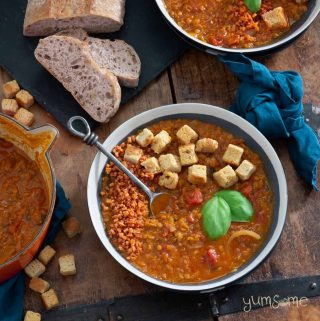 Overhead shot of several bowls of crockpot tomato lentil soup on a wooden table, with croutons scattered around, plus a cut loaf of bread on a black slate.