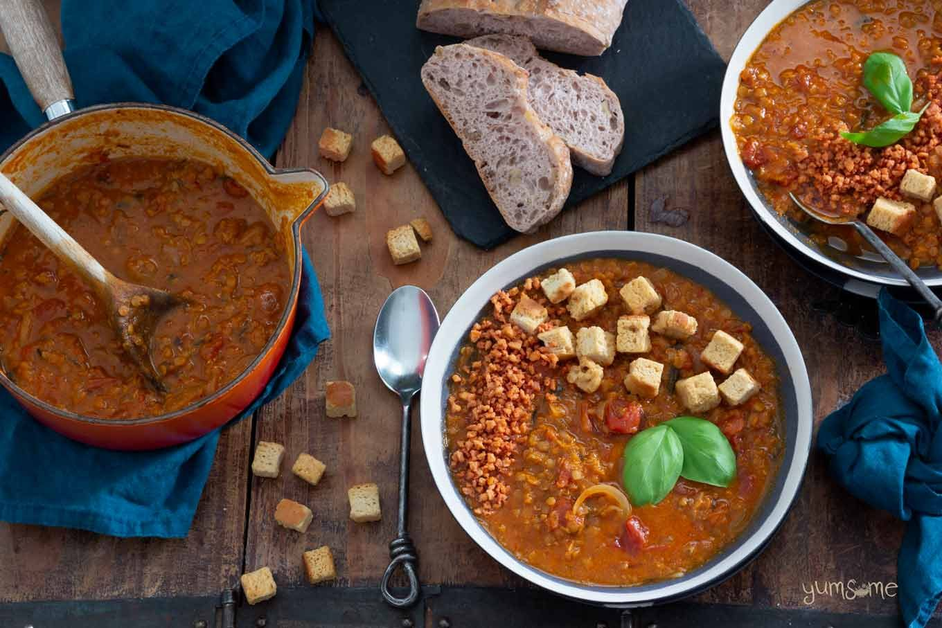 Several bowls and a pan of crockpot tomato lentil soup, plus bread and croutons on a wooden table.