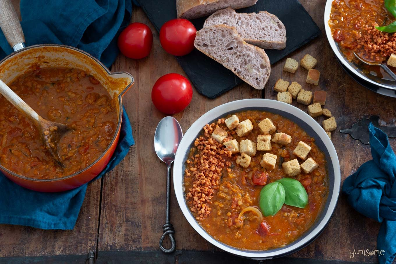 Several bowls and a pan of crockpot tomato lentil soup on a wooden table, with croutons, bread, and tomatoes.