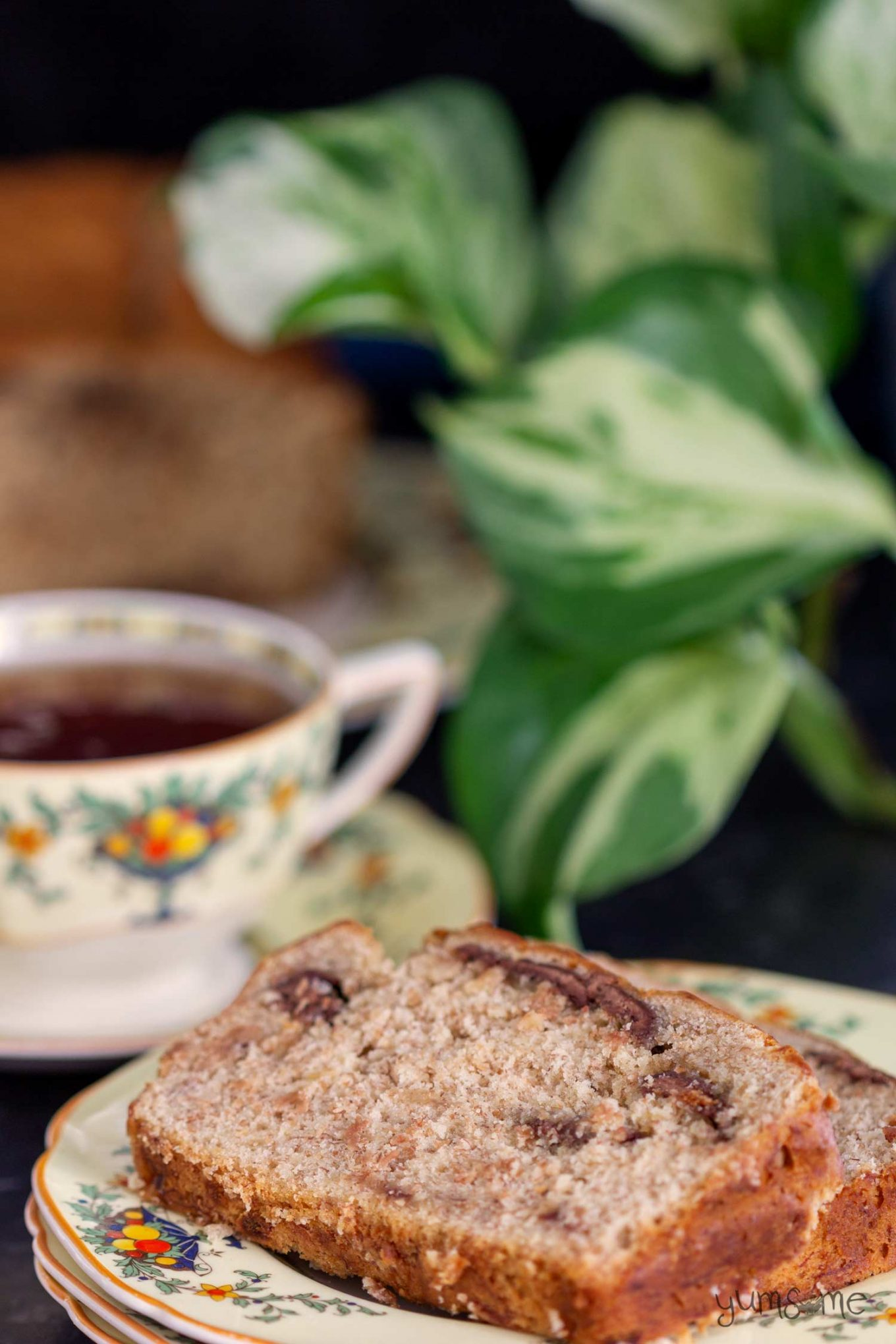 A cup of tea and a slice of chocolate chip banana bread.