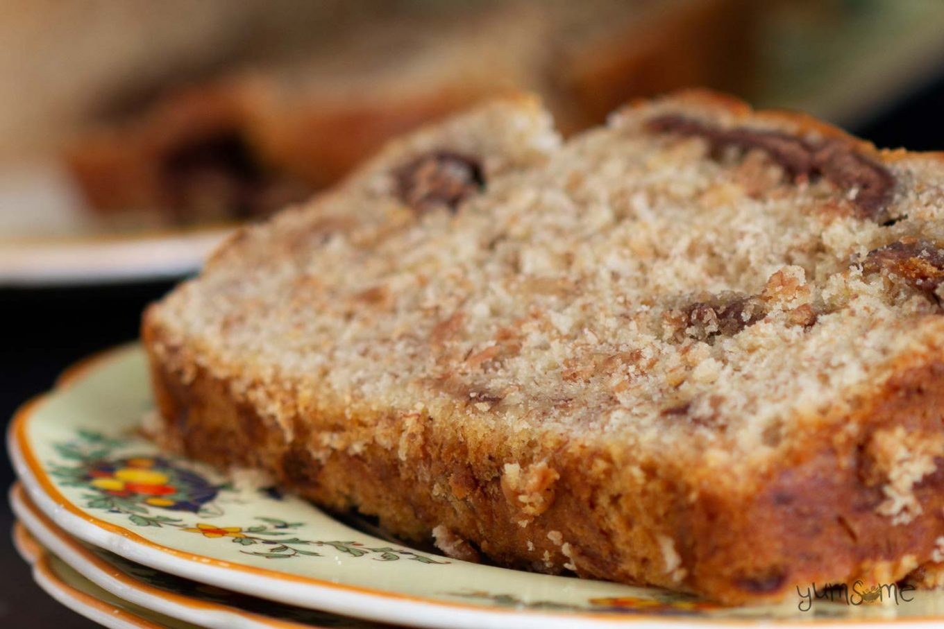 A closeup shot of a slice of chocolate chip banana bread on a yellow plate.