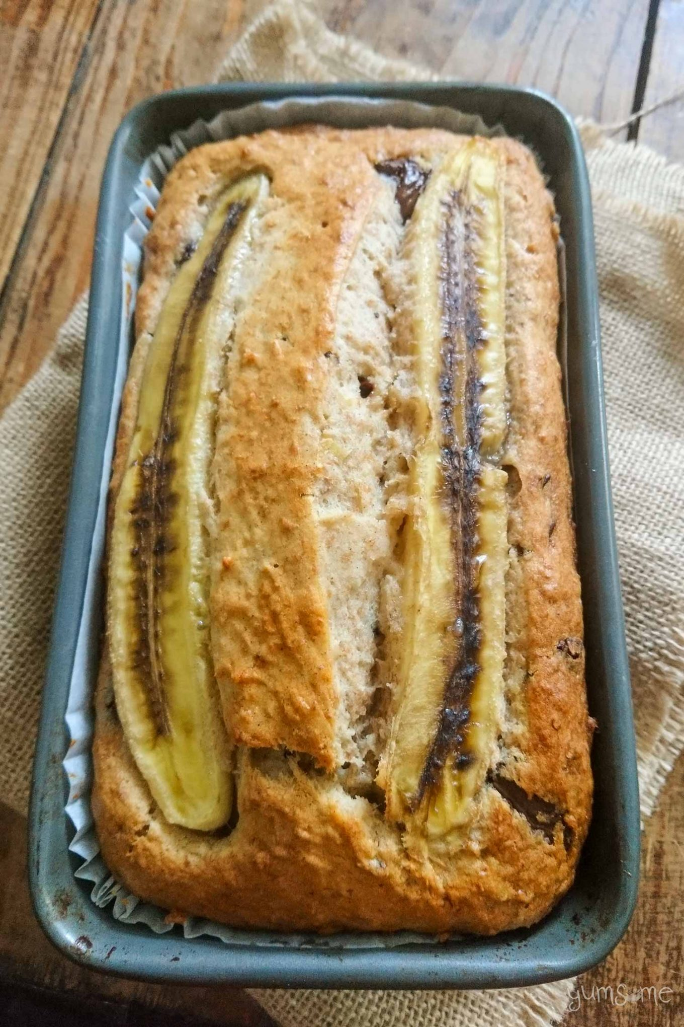Chocolate chip banana bread in a loaf pan, with sliced banana on top.