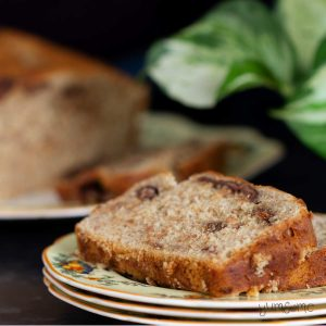 Two slices of chocolate chip banana bread on a stack of plate with a loaf and a green plant.